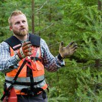 En man berättar i granskogen.